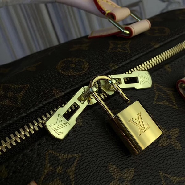 There is a small brass lock with the Louis Vuitton logo printed on it